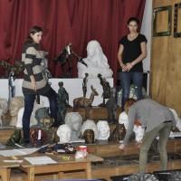 Trzy uczennice ustawiają prace uczniów ZSP w Lublinie wystawione na corocznej aukcji w szkolnej auli. Kliknięcie w miniaturkę obrazka spowoduje wyświetlenie powiększonego zdjęcia.