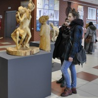 "Exhibition of works by ZSP students: in the ""Gala"" shopping center in Lublin. There are wood carvings and artwork on the walls in the lobby. Two students of the ZSP in Lublin are watching the sculpture. Clicking on the image thumbnail will display the enlarged photo."