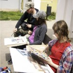 During the open-air painting, two students sit with their works. Teacher Grzegorz Tomczyk leaning over one student. Doing proofreading work. Clicking on the image thumbnail will display the enlarged photo..