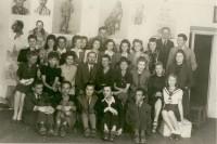 Mal-und Zeichenschule 1943/1944. Nauczyciele i uczniowie na tle prac z rysunku. Dyr Janina Miłosiowa (drugi rząd od dołu, piąta z lewej). Kliknięcie w miniaturkę obrazka spowoduje wyświetlenie powiększonego zdjęcia.