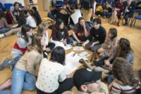 W auli szkolnej młodzież w grupach mieszanych polsko-izraelskich siedzą na podłodze tworząc okręgi. W środku leżą ołówki i arkusze papieru Kliknięcie w miniaturkę obrazka spowoduje wyświetlenie powiększonego zdjęcia.