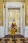 Eliza Kołodziej stoi w Sali Balowej. Trzyma w rękach dyplom w bordowej teczce z napisem koloru złotego. Kliknięcie w miniaturkę obrazka spowoduje wyświetlenie powiększonego zdjęcia.