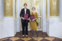 Anna Myszkowiak, Eliza Kołodziej stoją w Sali Balowej. Trzymają w rękach dyplomy w czerwonych teczkach. Kliknięcie w miniaturkę obrazka spowoduje wyświetlenie powiększonego zdjęcia.