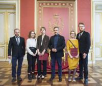 Stypendystki z dyplomami w rękach i osoby towarzyszące stoją przed tronem Stanisława Augusta Poniatowskiego. Kliknięcie spowoduje wyświetlenie powiększonego zdjęcia.