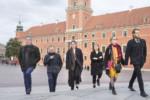 Od lewej: K. Dąbek, G. Tomczyk, M. Myszkowiak, A. Myszkowiak, E. Kołodziej i E. Małecki idą przez Plac Zamkowy. W tle widać Zamek Królewski w Warszawie. Kliknięcie spowoduje wyświetlenie powiększonego zdjęcia.