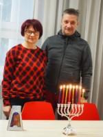 Alina Tkaczyk i Krzysztof Dąbek stoją stoją przy stole, na którym znajdują się zapalone chanukowe świece. Kliknięcie w miniaturkę obrazka spowoduje wyświetlenie powiększonego zdjęcia.