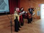 Cztery kobiety ubrane w czarne suknie i kolorowe, ludowe chusty. Trzy śpiewają Jedna z nich gra na instrumencie ludowym szarpanym. Mężczyzna w ciemnym garniturze gra na skrzypcach. Występują na scenie auli. Kliknięcie w miniaturkę obrazka spowoduje wyświetlenie powiększonego zdjęcia.
