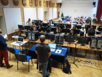 Uczniowie i nauczyciele siedzą przy zestawach komputerowych. Przy scenie dwóch mężczyzn z laptopami na stolikach, którzy prowadzą warsztaty. Kliknięcie w miniaturkę obrazka spowoduje wyświetlenie powiększonego zdjęcia.