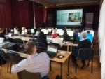 Uczniowie i nauczyciele siedzą przy zestawach komputerowych. Przy scenie mężczyzna, który prowadzi warsztaty. Na ekranie na scenie wyświetlony jest slajd. Kliknięcie w miniaturkę obrazka spowoduje wyświetlenie powiększonego zdjęcia.