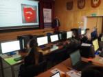 Uczniowie siedzą przy zestawach komputerowych. Przy scenie mężczyzna, który prowadzi warsztaty. Na ekranie na scenie wyświetlony jest slajd. Kliknięcie w miniaturkę obrazka spowoduje wyświetlenie powiększonego zdjęcia.