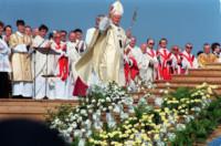 Scena dzieje się na dworze. Papież Jan Paweł II pozdrawia ludzi uniesioną dłonią. Za nim stoi dużo duchownych. Niżej na schodach kwiaty białe i żółte. Kliknięcie w miniaturkę obrazka spowoduje wyświetlenie powiększonego zdjęcia.
