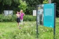 Dwie kobiety oglądają wystawę na terenach zieleni wokół szkoły. Jedna z nich fotografuje. Kliknięcie w  miniaturkę obrazka spowoduje wyświetlenie powiększonego zdjęcia.