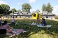 Pięciu młodych uczestników warsztatów maluje lub rysuje, klęcząc lub siedząc na trawie koło budynku Galerii Labirynt. Kliknięcie w miniaturkę obrazka spowoduje wyświetlenie powiększonego zdjęcia.