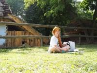 W słoneczny dzień uczennica w chuście na głowie siedzi na trawie i rysuje na kartonie położonym przed sobą. Za nią znajdują się: ogrodzenie, takie jak dla bydła, dwie wiejskie drewniane chaty pokryte strzechą, drzewa. Kliknięcie w miniaturkę obrazka spowoduje wyświetlenie powiększonego zdjęcia.