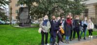 Grupa uczniów stoi przed pomnikiem im. Józefa Czechowicza przy ul. Krakowskie Przedmieście w Lublinie. Młodzież jest w maseczkach z powodu obostrzeń sanitarno-epidemiologicznych. Kliknięcie w miniaturkę obrazka spowoduje wyświetlenie powiększonego zdjęcia.