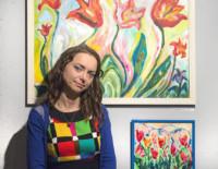 Dorota Jurkowska na tle swoich prac w galerii. Kliknięcie w miniaturkę obrazka spowoduje wyświetlenie powiększonego zdjęcia.większonego zdjęcia.