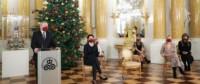 Prof. Piotr Gliński podczas konferencji prasowej online, transmitowanej z Sali Wielkiej Zamku Królewskiego w Warszawie. Stoi przy mównicy i przemawia. Po jego lewej stronie siedzi pięć kobiet z zachowaniem odległości. Wszyscy mają bordowe maski na twarzach. Jest też duża, udekorowana choinka i szopka bożonarodzeniowa. Fot. Danuta Matloch. Kliknięcie w miniaturkę obrazka spowoduje wyświetlenie powiększonego zdjęcia.