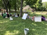 Jest ciepło i słonecznie. W skansenie znajdują się: wiejskie drewniane chaty pokryte strzechą, drewniane płoty, dużo zieleni. Młodzież rysuje i maluje na bertramach umieszczonych na sztalugach lub opartych o pień drzewa. Koło uczniów siedzi na trawie biała koza. Kliknięcie w miniaturkę obrazka spowoduje wyświetlenie powiększonego zdjęcia.