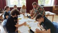 Młodzież (pięć osób) rysuje i maluje sceny komiksu w auli szkolnej. Grzegorz Nowicki tłumaczy. Kliknięcie w miniaturkę obrazka spowoduje wyświetlenie powiększonego zdjęcia.