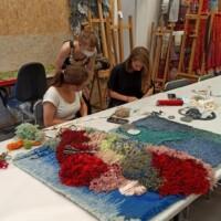 Dwie uczennice i  Anna Łoś (nauczyciel) pracują w czasie  warsztatów w pracowni szkolnej (tkanina art). Kliknięcie w miniaturkę obrazka spowoduje wyświetlenie powiększonego zdjęcia.