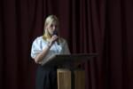 Uczennica przemawia w auli szkolnej. Kliknięcie w miniaturkę obrazka spowoduje wyświetlenie powiększonego zdjęcia.