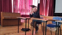 Leszek Mądzik w auli szkolnej. Kliknięcie w miniaturkę obrazka spowoduje wyświetlenie powiększonego zdjęcia.