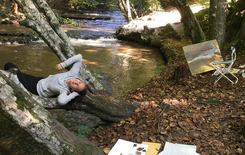 Uśmiechnięta dziewczyna leży na pniu drzewa nad rzeką obok obrazu. Kliknięcie w obrazek spowoduje przejście do artykułu.