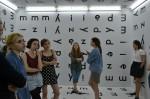 Grupa uczennic ZSP w Lublinie oglądają wystawę. Są w letnich ubraniach. W całym pomieszczeniu naklejone litery: na ścianach, suficie i podłodze. Kliknięcie w miniaturkę obrazka spowoduje wyświetlenie powiększonego zdjęcia.