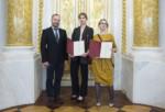 Od lewej: G. Tomczyk, M. Myszkowiak i E. Kołodziej stoją w Sali Balowej. Dziewczęta pokazują dyplomy w bordowych teczkach. Kliknięcie spowoduje wyświetlenie powiększonego zdjęcia.