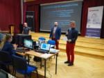 Dyr Krzysztof Dąbek przemawia. Obok dwóch mężczyzn, którzy prowadzą warsztaty. Na ekranie na scenie wyświetlony jest slajd. Kliknięcie w miniaturkę obrazka spowoduje wyświetlenie powiększonego zdjęcia.
