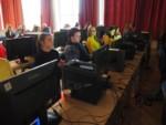 Uczniowie siedzą przy zestawach komputerowych. Kliknięcie w miniaturkę obrazka spowoduje wyświetlenie powiększonego zdjęcia.