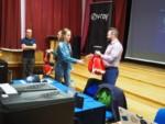 Uczennica odbiera prezent od mężczyzny prowadzącego warsztaty na środku auli, przy scenie. Kliknięcie w miniaturkę obrazka spowoduje wyświetlenie powiększonego zdjęcia.