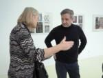 Na tle prac w galerii dyr Krzysztof Dąbek rozmawia z nauczycielką Małgorzatą Przygrodzką. Obok stoi Marzena Łukaszuk. Kliknięcie w miniaturkę obrazka spowoduje wyświetlenie powiększonego zdjęcia.