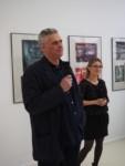Na tle prac w galerii dyr Jarosław Ćwiek przemawia. Obok stoi Marzena Łukaszuk. Kliknięcie w miniaturkę obrazka spowoduje wyświetlenie powiększonego zdjęcia.