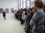 Marzena Łukaszuk przemawia na tle prac w galerii. Obok stoją ludzie, w większości młodzież. Kliknięcie w miniaturkę obrazka spowoduje wyświetlenie powiększonego zdjęcia.