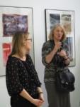 Na tle prac w galerii Małgorzata Przygrodzka przemawia. Obok stoi Marzena Łukaszuk. Kliknięcie w miniaturkę obrazka spowoduje wyświetlenie powiększonego zdjęcia.