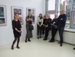 Na tle prac w galerii Małgorzata Przygrodzka przemawia. Po jej lewej stronie stoi Marzena Łukaszuk, po prawej ludzie. Kliknięcie w miniaturkę obrazka spowoduje wyświetlenie powiększonego zdjęcia.