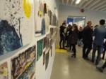 Ludzie, w większości młodzież oglądają wystawę. Kliknięcie w miniaturkę obrazka spowoduje wyświetlenie powiększonego zdjęcia.