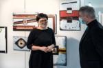 Agnieszka Wójtowicz i dyr Krzysztof Dąbek (rozmawiają) na tle obrazów w galerii. Kliknięcie w miniaturkę obrazka spowoduje wyświetlenie powiększonego zdjęcia.
