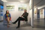 Dorota Jurkowska i dyr Krzysztof Dąbek rozmawiają ze sobą siedząc na krzesłach w galerii na tle prac artystki. Kliknięcie w miniaturkę obrazka spowoduje wyświetlenie powiększonego zdjęcia.