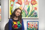 Dorota Jurkowska na tle swoich prac w galerii. Kliknięcie w miniaturkę obrazka spowoduje wyświetlenie powiększonego zdjęcia.