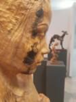 Zbliżenie na twarz i wykadrowanie. Popiersie kobiety z okrągłym przedmiotm w ręce i z otworem w piersi z prawej strony. Kliknięcie w miniaturkę obrazka spowoduje wyświetlenie powiększonego zdjęcia.